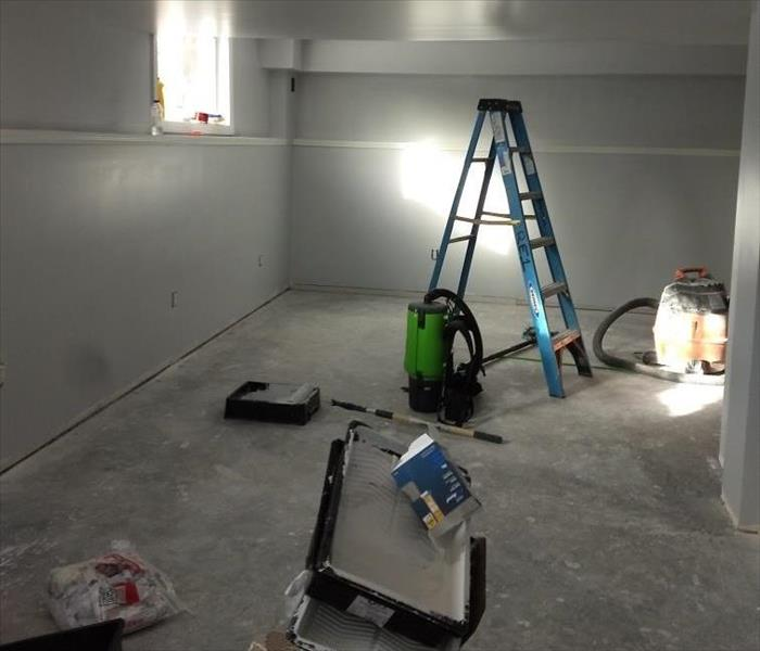 A view of a corner of a damaged basement, floors removed, with a ladder and SERVPRO drying and cleaning equipment throughout