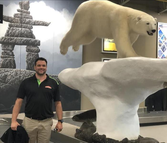 Owner standing beside Polar Bear statue at Yellowknife Airport