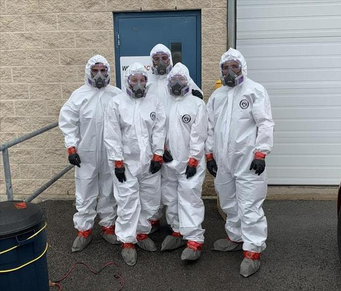 Five SERVPRO of Barrie employees dressed in white hazmat suits, standing in front of a Canadian warehouse building.