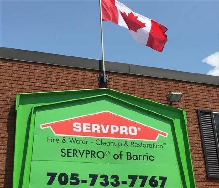 Looking up at the SERVPRO of Barrie Sign on the front of our building, with the Canadian Flag hanging above it.