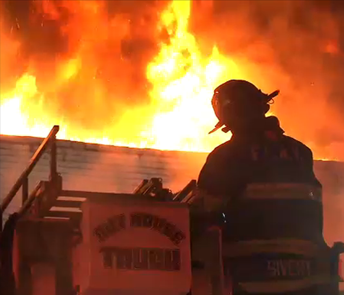 Firefighter is standing on his firetruck, looking up at a huge fire engulfing a local business.